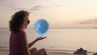 Woman holding Earth Hologram in hand near sea.  glowing and shining futuristic interface