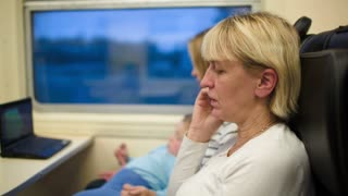 Woman in the train talking on the phone. Mother with son watching movie in background