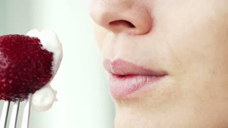 Woman licking lips in front of strawberry, super slow motion, shot at 240fps
