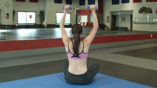 Woman Lifting Dumbbells Over Her Head 2