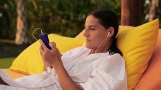Woman listening music in the garden and lying on bed