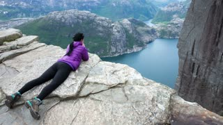 Woman looking at the landscape from a height. Beautiful Nature Norway Preikestolen or Prekestolen.