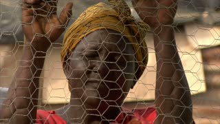 Woman looking through fence