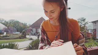 Woman looking through menu. 4K, Ultra HD. Dolly shot. Lifestyle: young beautiful female reading a menu in an outdoor cafe, getting ready to make an order. Restaurant terrace.