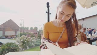 Woman looking through menu. Slow Motion 120 fps. Dolly shot. Lifestyle: young beautiful female reading a menu in an outdoor cafe, getting ready to make an order. Restaurant terrace.