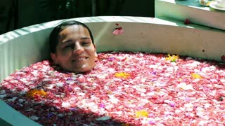 Woman lying in bath and smiling to the camera