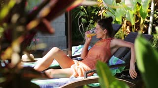 Woman lying on sunbed and drinking orange juice