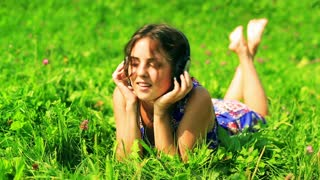 Woman lying on the meadow and enjoying listening music on headphones