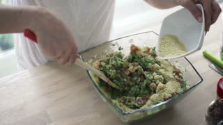 Woman mixing salad with wooden spoon and adding couscous kasha, slow motion shot at 240fps