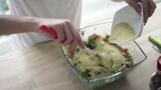 Woman mixing salad with wooden spoon and adding couscous kasha, slow motion shot at 480fps