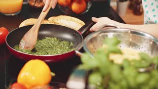 Woman preparing meal at the kitchen, Slow Motion 120 fps, dolly shot. Young woman cooking spinach greens on the frying pan. Vegetarian, healthy, home made food. 4K