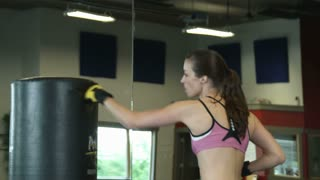 Woman Punching a Punching Bag Near Mirror