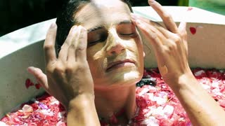 Woman putting mask on her face, relaxing in the spa