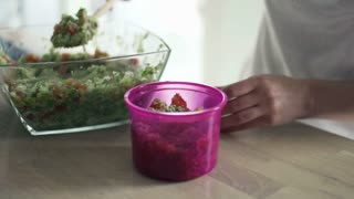 Woman putting salad into plastic box in kitchen, slow motion shot at 240fps