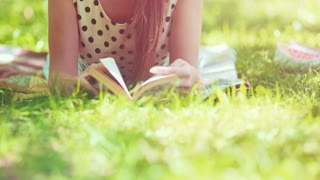 Woman reading a book in the park outdoors. Slow motion. Beautiful romantic lady in white hat laying on the green grass lawn and looking through the novel pages and daydreaming on a sunny day. 4K, DCi.