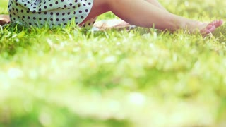 Woman reading a book in the park outdoors. Slow motion. Dolly shot. Beautiful romantic lady in white hat sitting on the green grass lawn and looking through the novel pages and daydreaming. 4K, DCi.