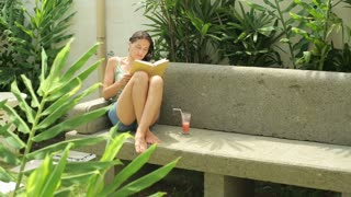 Woman reading book in the garden on bench