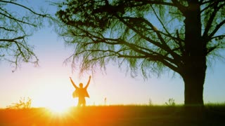 woman running at sunrise under trees while warming up