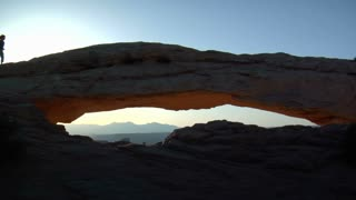 Woman Runs Across Mesa Arch Canyonlands National Park