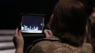 Woman shooting performance on the stage with touchpad. Back view.