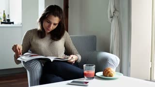 Woman sitting in armchair and reading magazine at home