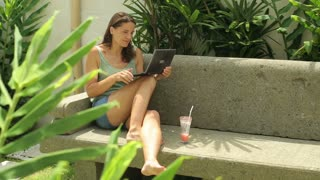 Woman sitting in the garden and chatting on laptop