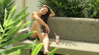 Woman sitting on bench in exotic garden and smiling to the camera