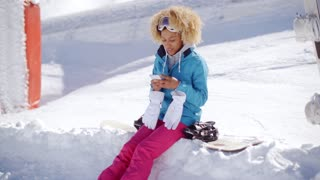 Woman sitting on snowbank texting