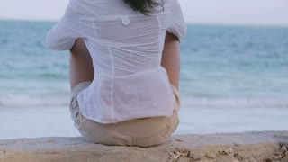 Woman sitting on the beach and relaxing, steadycam shot