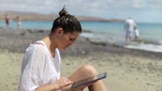 Woman sitting on the beach with tablet, family in background