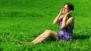 Woman sitting on the meadow and listening music on headphones