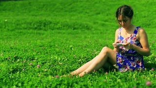 Woman sitting on the meadow and typing message on smartphone