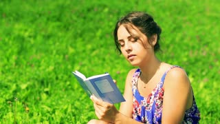 Woman sitting on the meadow and writing sad memories in the notebook