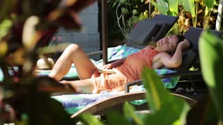 Woman sleeping on sunbed in tropical place