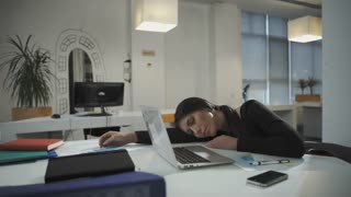 Woman tired from working long stressful hours, takes a phone call