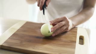 Woman slicing onion on chopping board in kitchen, slow motion shot at 240fps