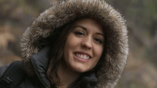 woman smiles as snow falls on her jacket hood