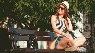 Woman smiling and sitting on a bench in the European city. Slow Motion, 4K. Happy Beautiful Hipster girl enjoying the sun and the life. Travel in style. Lens flare.