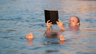 Woman smiling as she reads a book while swimming floating on her back in the water holding the book in the air
