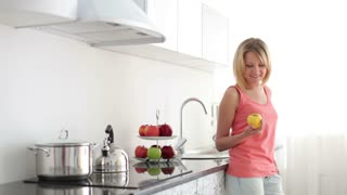 Woman standing at kitchen with apple and smiling