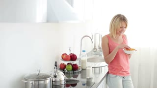 Woman standing in kitchen and eating cornflakes