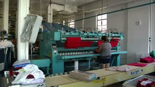 Woman Takes Red Cloth From Industrial Ironing Machine