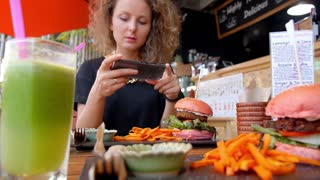 Woman Taking Picture of Veggie Burger with Mobile Phone in Healthy Cafe