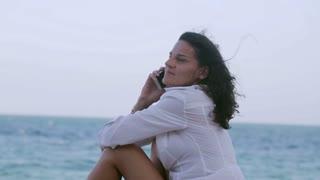 Woman talking on cellphone on the beach, steadycam shot