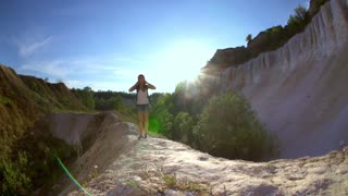 Woman tourist hiking in mountains. Athletic sportive tourist woman is hiking in a sunny mountain canyon and enjoying the view and the adventure. Slow motion filmed at 240 fps.