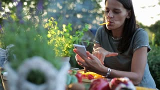 woman using a cellphone and eating pepper in the garden