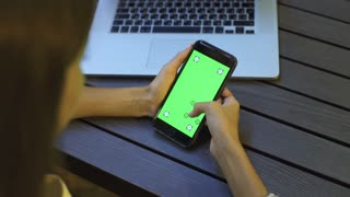 Woman using a mobile phone with green screen and scrolling. Green screen for your custom video content with corner has marks for advanced tracking