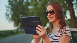 Woman using digital tablet by the car. Filmed in 4K DCi resolution. Young smiling woman by the car using digital tablet navigation and internet on a road. Travel and technology. Slow motion.