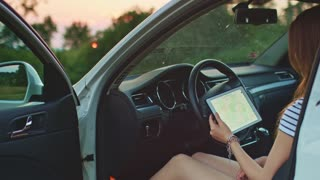Woman using digital tablet in the car. Filmed in 4K DCi resolution. Young woman in a car reading road map and looking for navigation directions in a tablet. Travel and technology. Slow motion.
