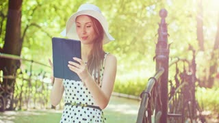 Woman using digital tablet in the green park outdoors. Beautiful young lady, wearing a hat and a dress, using a modern tablet to search for information and communicate in summer. Slow motion. 4K, DCi.